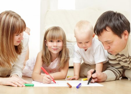 Photo for Parents with children drawing laying on a floor - Royalty Free Image