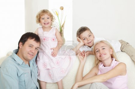 Photo for Happy family with two children on sofa - Royalty Free Image