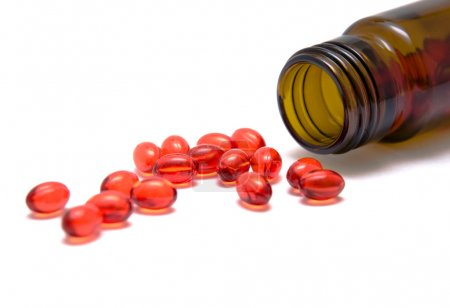 Photo pour Pilule rouge de la bouteille sur fond blanc - image libre de droit