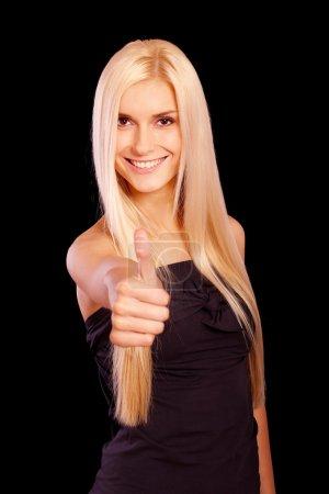 Foto de Hermosa joven levanta el pulgar lo que significa que todo notable, se aisló en fondo negro - Imagen libre de derechos