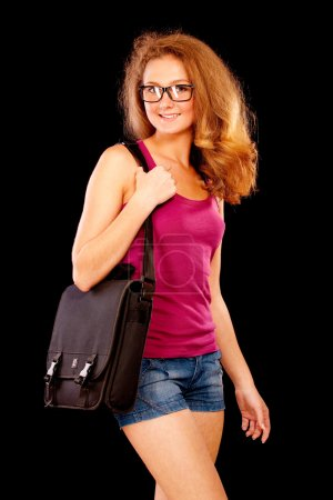 Photo for Nice girl-student holds on shoulder bag with textbooks, it is isolated on black background. - Royalty Free Image