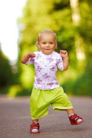 Photo pour La petite fille va vigoureusement sur le chemin asphalté . - image libre de droit
