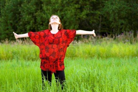 Photo pour La jeune belle femme a étendu les mains dans tous les sens sur une prairie verte . - image libre de droit