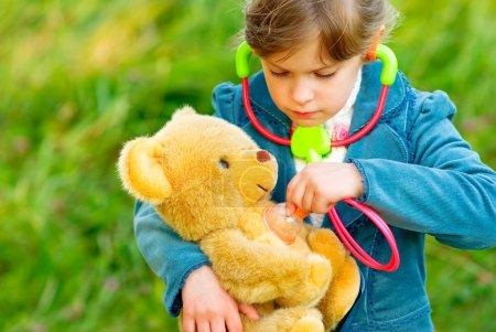 Girl listens stethoscope to plush bear