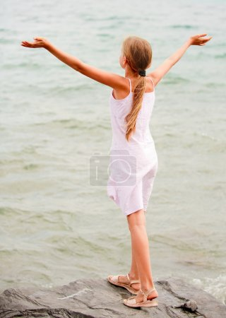 Photo for Young schoolgirl stands on seacoast and lifts hands towards to summer sun. - Royalty Free Image