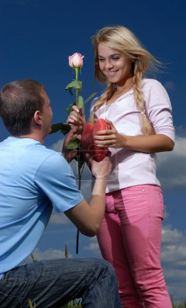 Young man gives a rose and heart