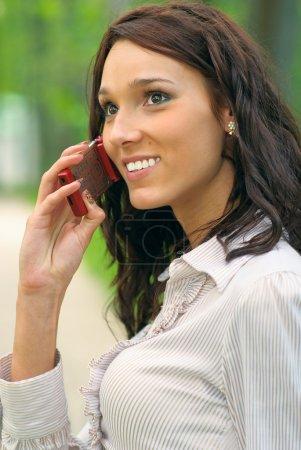 Brunette speaks on cellular telephone