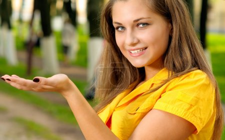 Photo pour Jeune fille en robe jaune détient sur palm vos marchandises - image libre de droit