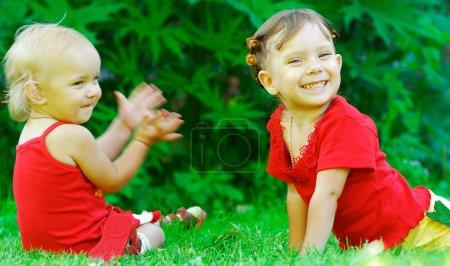 Photo pour La petite fille des claques mains ensemble, comme il a aimé un poème gai qui a dit à sa sœur. - image libre de droit