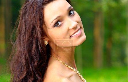 Foto de Sonrisas de mujer hermosa joven contra la madera de verano. - Imagen libre de derechos