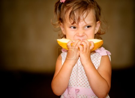 Photo for Little girl eats piece of juicy yellow melon. - Royalty Free Image