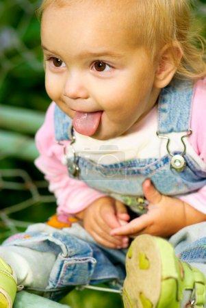 Foto de Niño pequeño con overoles pantalones vaqueros saca lengua. - Imagen libre de derechos