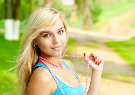 Photo for Beautiful girl with pink beads against summer garden. - Royalty Free Image
