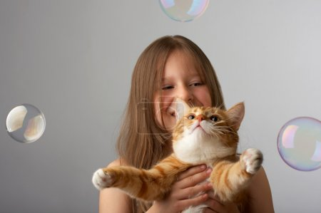 Small girl with a red cat