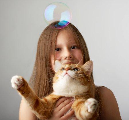 Photo pour Le siège de la petite fille, bulles de savon détient un chat rouge et elle attrape - image libre de droit