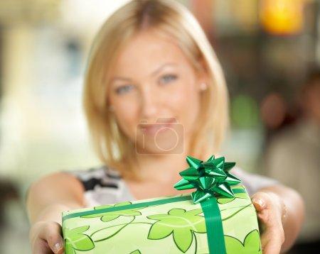 Photo pour La jolie jeune fille sourit et fait un cadeau en emballage - image libre de droit