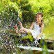 The playful girl sprays feet pond water...