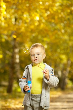 Photo for The happy kid plays in the autumn in park - Royalty Free Image