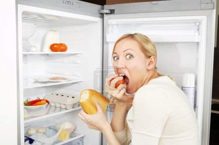 Photo for The woman greedy eats meal against an open refrigerator - Royalty Free Image