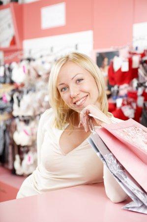 Foto de La rubia sonriente en tienda de los costes de sujetadores en un mostrador - Imagen libre de derechos