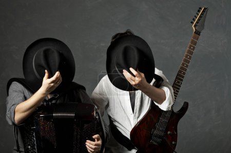 Photo for Two musicians with a guitar and an accordion close the face hats - Royalty Free Image