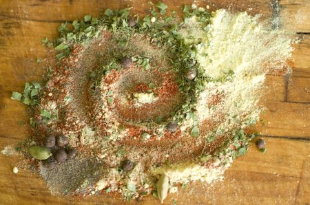 Photo for А blend of fragrant pepper, grains of green cardamom, ground paprika, black pepper, asafoetida and dried greens on an old wooden breadboard. - Royalty Free Image
