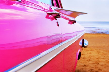 Classic pink Cadillac at beach