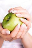 Green apple in women's hands