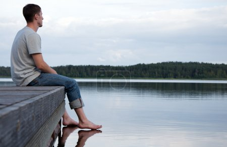 Photo pour Un jeune homme assis seul par l'eau - image libre de droit