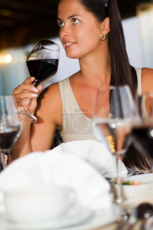 Beautiful woman tasting red wine