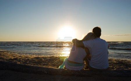 Photo pour Couple assis près de la mer au coucher du soleil - image libre de droit