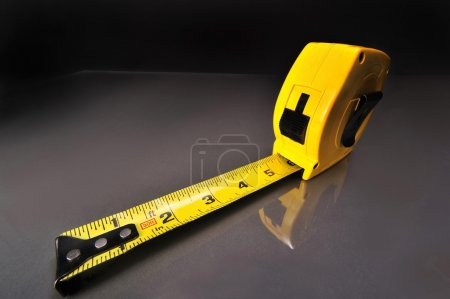 Photo for Yellow tape measure on gray table top. - Royalty Free Image