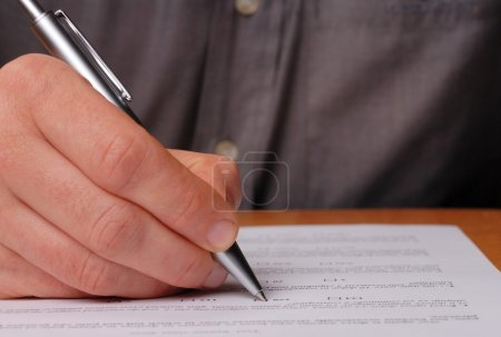 Photo pour Quelqu'un remplissant un examen ou un autre formulaire de test - image libre de droit