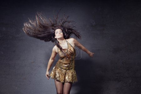 Photo for Woman dancing and moving her long hairs on a trashy background - Royalty Free Image