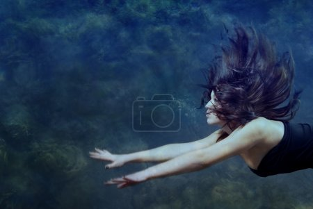 Photo for Beautiful lady swimming and diving underwater - Royalty Free Image