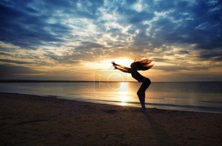 Photo pour Femme dynamique danse sur la plage pendant le coucher du soleil - image libre de droit