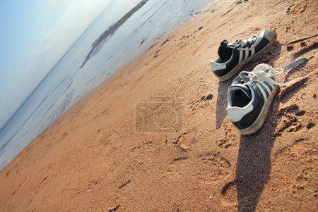Photo pour Deux chaussures du voyageur à la plage d'été - image libre de droit