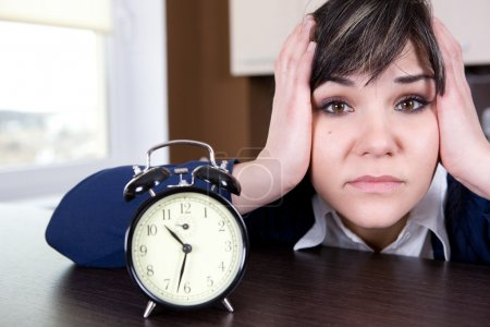 Attractive brunette and tired woman with clock...