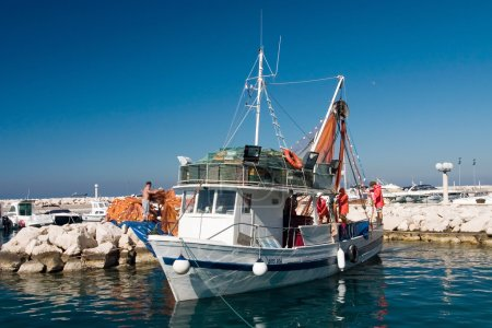 Few fishermans prepare shrimp boat to sail out...