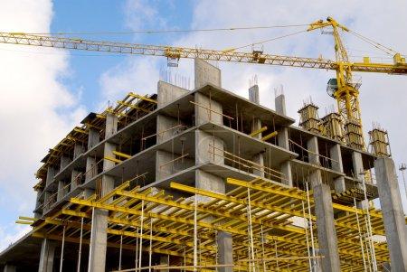 Photo pour Grue près de construction sur fond de ciel couvert - image libre de droit