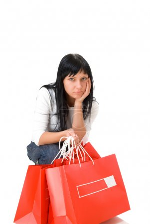 Photo pour Jolie fille triste tenant des sacs à provisions. Isolé sur fond blanc - image libre de droit