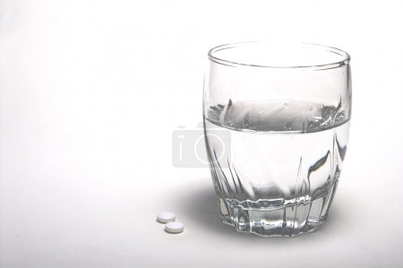 Photo for Two aspirin and a glass of water. - Royalty Free Image
