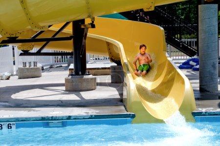 Photo pour Un jeune garçon glissant sur une glissière d'eau . - image libre de droit