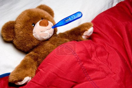 Photo for A sick teddy bear with a thermometer in his mouth. - Royalty Free Image