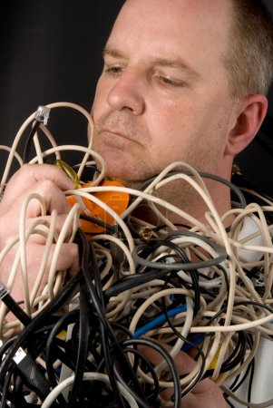 A man tangled up in wires and cables....