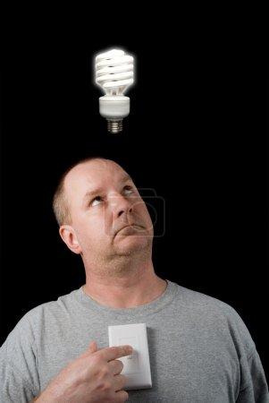 Photo pour Un homme regardant une ampoule allumée au-dessus de sa tête. - image libre de droit