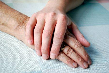 Photo pour Gros plan de deux mains sur la table avec lumière du jour . - image libre de droit