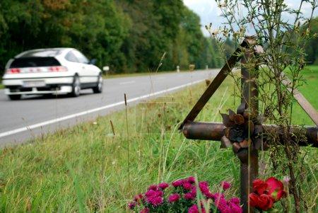Photo pour Croix avec des fleurs sur le bord d'une route de campagne pour le mémorial des nombreuses victimes de l'accident - image libre de droit