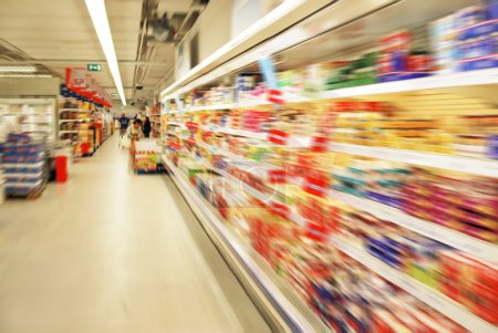 Photo for Blurred shopping in a supermarket with shelves - Royalty Free Image