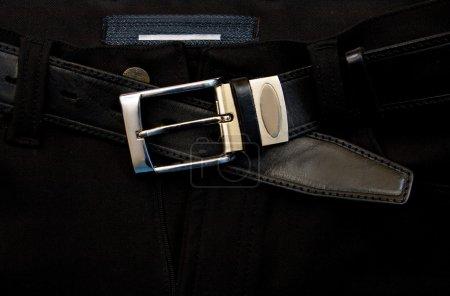 Unfastened a strap on black jeans